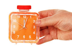 Orange alarm clock in a hand on a white background. Royalty Free Stock Image