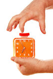 Orange alarm clock in a hand on a white background. Stock Photos