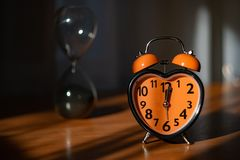 An orange alarm clock is on the table. In the background - hourglass stock photo
