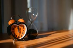 An orange alarm clock is on the table. It shows the dinner time. In the background - hourglass. It symbolizes the past stock photo
