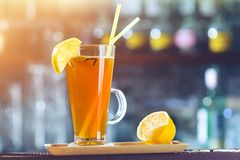 Orange alkoholiserad coctail i ett exponeringsglas med citronen och sugrör på lodisar royaltyfria foton