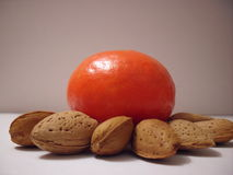 Orange with almonds. Orange surrounded by brown almonds Stock Photo