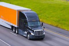 Orange Anhänger des schwarzen modernen halb LKWs, der Landstraßenlinie fährt stockbilder
