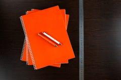 Orange anteckningsböcker som ligger på en trätabell för mörk brunt med apelsin- och vitpennor och ett måttband Arkivbild