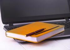 Orange anteckningsbok med en blyertspenna som ligger på en bärbar dator Royaltyfri Bild