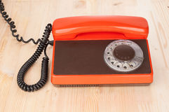 Orange antique phone on wooden desk. Orange antique phone closeup on wooden desk Royalty Free Stock Photos