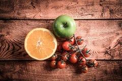 Orange Apfel und Tomate auf Holztisch Stockbild