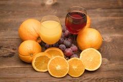 Orange, Apfel und Traubensaft und Früchte auf einem hölzernen Hintergrund stockbild