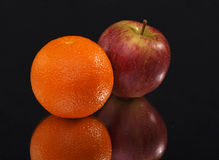 Orange and apple on black background Royalty Free Stock Images