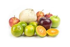 Orange, apple and coconut piled white . Royalty Free Stock Photo