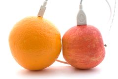 The orange and apple are connected 2. The orange and apple are connected through a cable 2 Stock Image