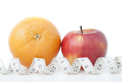 Orange and apple with a measuring tape. On a white background Stock Photos