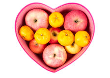 Orange and apple mixed in heart-shaped gift box on white Stock Photo