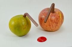 Orange and apple stab by straw and liquid red dot Royalty Free Stock Photo
