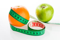 Orange and apple with tailor s ruler. Fruit healthy vitamin diet Stock Images