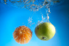 Orange and apple in water Royalty Free Stock Image
