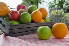 Orange and apple in a wooden crate. Fresh fruit on a wooden table with a cloth. Eating fruit helps to lose weight. fruits and stock image