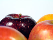 Orange and apples. 3 apples and an orange with focus on deep red apple royalty free stock photo