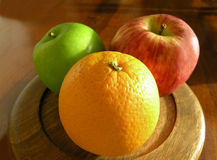 Orange and apples. A warm picture of an orange in the foreground and two apples behind Royalty Free Stock Image