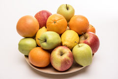 Orange, apples and banana on the wooden plate stock photo