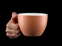 Orange - apricot color cup - mug on black background. Royalty Free Stock Photos