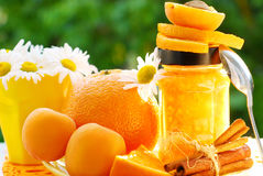 Orange and apricot jam. In jar on garden table Stock Photo