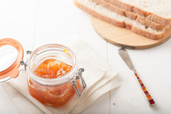 Orange or apricot jam with bread, shallow depth of Royalty Free Stock Images