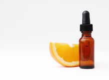 Orange Aromatherapy. Orange wedge next to an amber bottle of essential oil Stock Photos