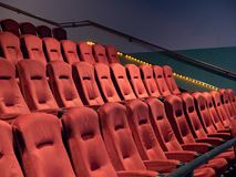 Orange, art deco fuzzy movie theater seats in an empty theater. Some orange, art deco fuzzy movie theater seats in an empty theater stock image