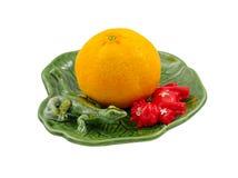 Orange auf dekorativem Teller mit der Eidechse und Kuh, lokalisiert Stockfotografie