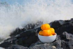 Orange auf den Felsen und den Wellen, die auf den Felsen spritzen Lizenzfreie Stockbilder