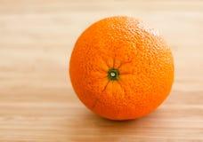 Orange auf einem hellen hölzernen Schneidebrett Lizenzfreie Stockfotografie