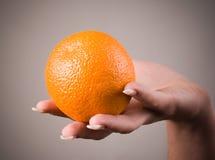 Orange auf einer Hand Stockfoto