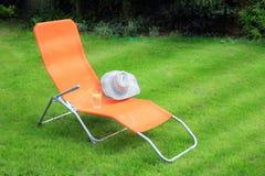 Orange Aufenthaltsraum sunbed Stellung auf grünem Gras lizenzfreies stockbild