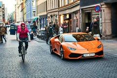 Orange Auto Lamborghinis Huracan LP 580-2 Spyder gab circa 2016 in Italien parkte auf der Straße mit einem Fahrradkurier frei Stockbild