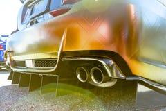 Orange Auto mit Doppelauspuffrohren auf Beton mit Linsengespür Lizenzfreies Stockbild