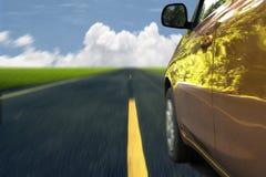 Orange Autoauf die Straße schnell fahren Stockfotos