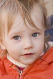 Orange baby. Little girl wiyh curious eyes in orange dress Royalty Free Stock Photos