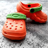 Orange Baby Shoes and Gray floor Royalty Free Stock Photos