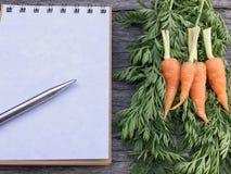 Orange Babykarotte auf grünem Blattholztischhintergrund und -notizbuch und Stift mit Stockbild