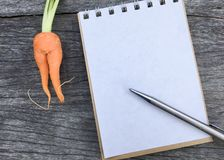 Orange Babykarotte auf hölzernem Hintergrund und Raumnotizbuch und -stift Stockfotos