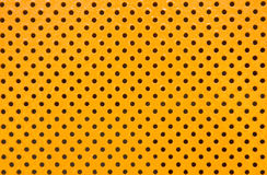 Orange Background. An orange metal sheets full of holes serving as a rough looking background royalty free stock image