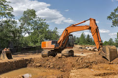 Orange backhoe on construction site. An orange backhoe sits on a construction site with a hole it has dug that has been filled with rainwater. Room for copy stock photography