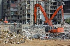 Orange Backhoes Demolish Building. Multiple orange backhoes work to raze a multi-story building Stock Photos