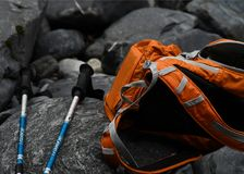 Orange backpack and blue walking sticks on rocks stock images