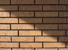 Orange Backsteinmauer mit Schatten-Winkel-Hintergrund-Beschaffenheit Stockbild