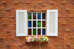 Orange Backsteinmauer und weißes hölzernes Fenster mit bunten Blumen Lizenzfreie Stockfotos