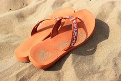 Orange badskor på sanden Royaltyfria Foton