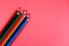 Orange bakgrund och färgade blyertspennor Fotografering för Bildbyråer