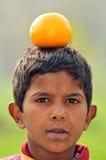 Orange balance. Portrait of a poor indian boy with orange on her head Stock Photos